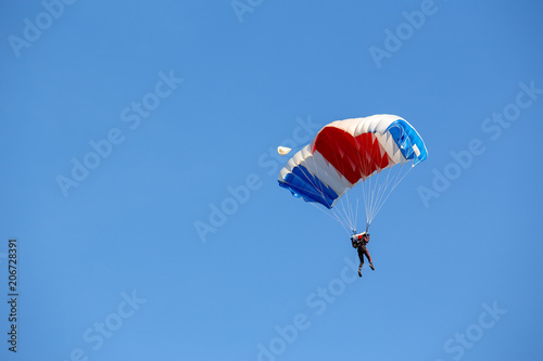 Poster Luchtsport isolated skydiver control colorful parachute gliding after free fall jump with blue sky background