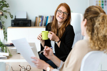 Two Pretty Young Business Woman Relaxing One Moment While Drinking Coffee In The Office.