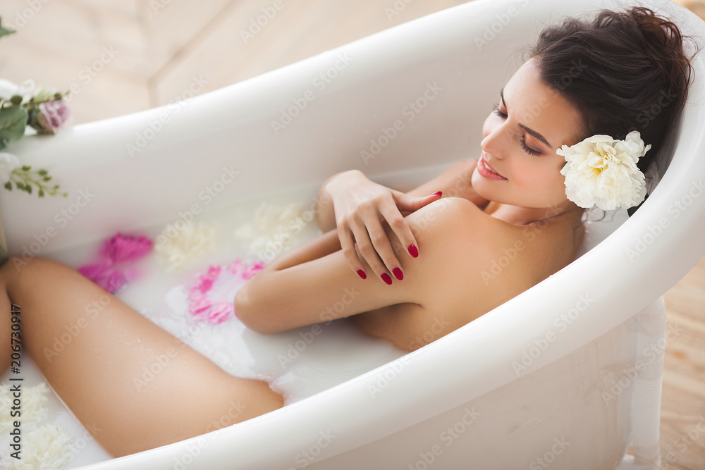 Fototapeta Young attractive woman taking bath with milk and flowers