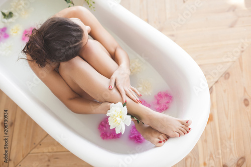 Leinwand Poster Young attractive woman taking bath with milk and flowers