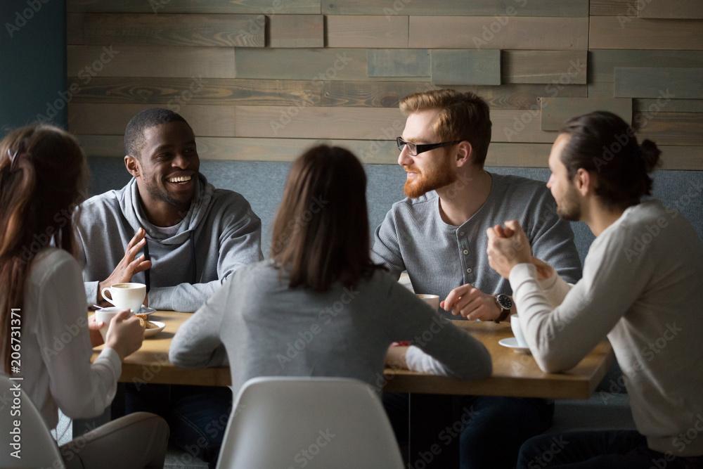 Fototapeta Multiracial young friends talking drinking coffee together sitting at cafe table, african man telling joke while diverse millennial smiling people enjoying listening having fun at coffeehouse meeting