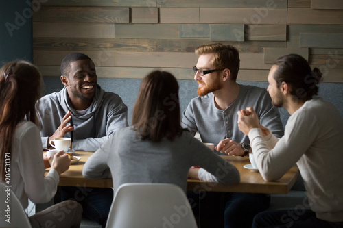 Fotografía  Multiracial young friends talking drinking coffee together sitting at cafe table