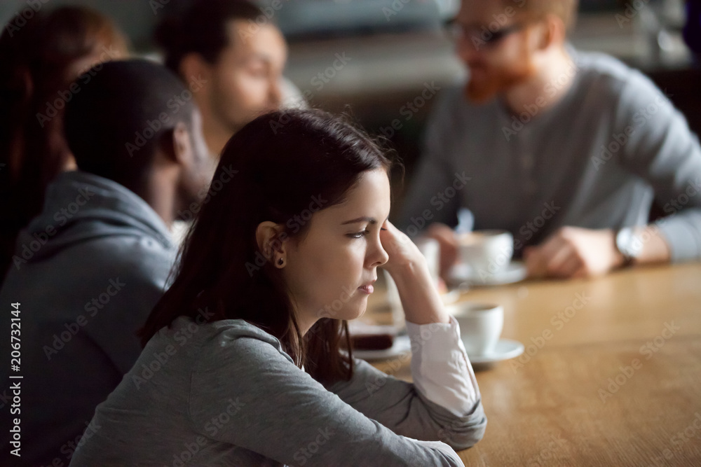 Fototapety, obrazy: Frustrated upset millennial girl sitting alone at cafe table after conflict ignoring friends, young woman feeling jealous rejected offended thinking of bad relations with boyfriend in public place