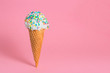 Leinwandbild Motiv funny creative concept of close up wafer cup with ice cream and colorful sprinkles on pink background, copy space