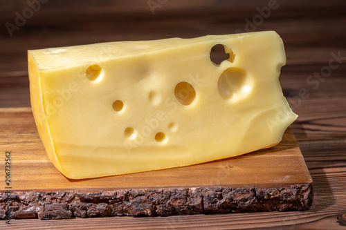 portion of fresh maasdam cheese on wooden table