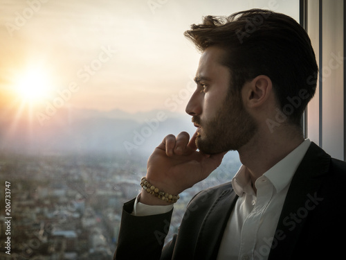 Fotografie, Tablou  Handsome serious businessman standing inside modern building next to big window,