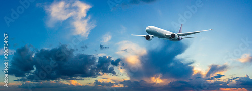 Fotografia  Passenger airplane flying above night clouds and amazing sky at the sunset