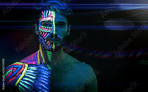 Photo  Young man painted in fluorescent paint on face and muscular torso, in studio sho