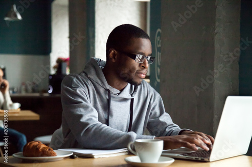 Serious millennial african-american man using laptop sitting at cafe table, focused black casual guy communicating online, writing emails, distantly working or studying on computer in public place
