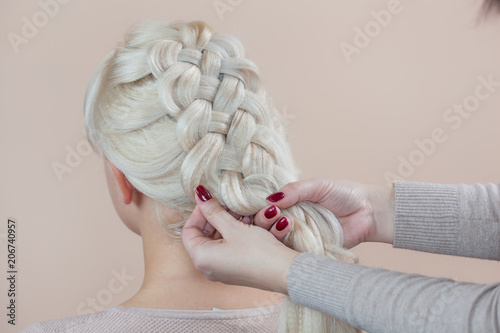 Beautiful girl with blonde hair, hairdresser weaves a  braid close-up, in a beauty salon. Professional hair care and creating hairstyles.