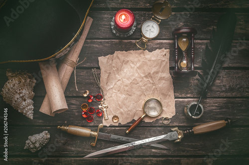 Fotomural Pirate captain table with crumpled paper page with copy space for treasure map, golden compass, sand watch, scrolls,gemstones, seashell and dagger
