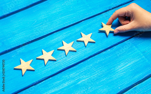 Fotografía  A female hand puts the fifth wooden star on a blue background