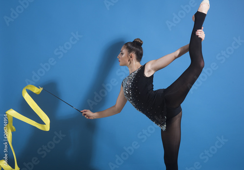 Spoed Foto op Canvas Gymnastiek beautiful Caucasian girl gymnast with yellow ribbon in split.