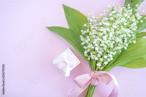 Pink gift box with engagement ring and bouquet of lilies of the valley on pink background with copy space