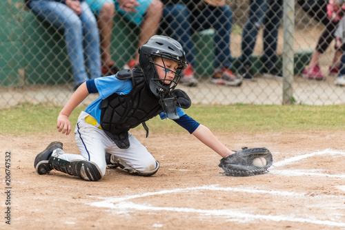 Agile little league baseball catcher lunging for a low pitch in the dirt in a cloud of chalk.