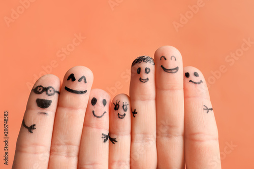 Fingers with drawings of happy faces against color
