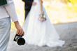 canvas print picture - Professional photographer with camera and wedding couple, outdoors