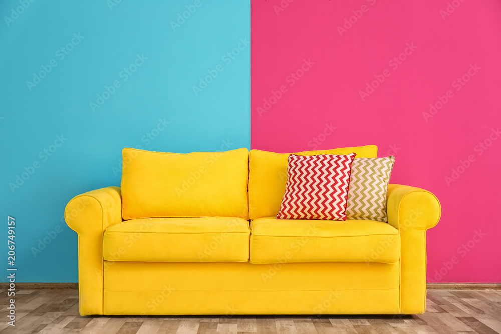 Fototapety, obrazy: Sofa with different pillows near color wall in room