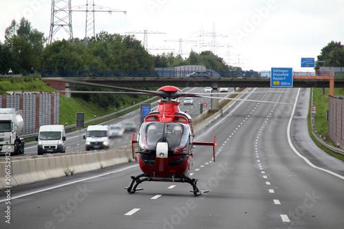 Ein Rettungshubschrauber steht auf einer deutschen Autobahn.