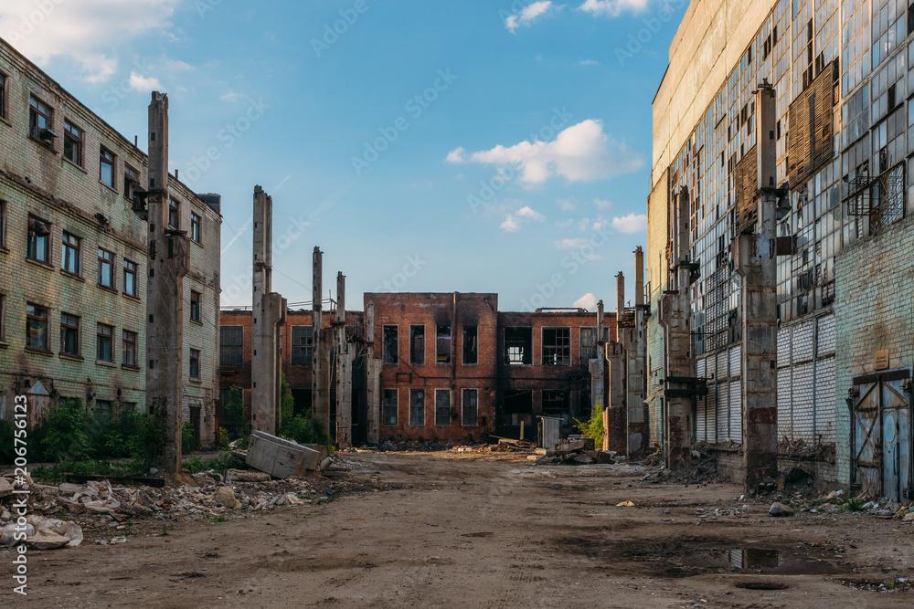 Fototapeta Territory of abandoned industrial area waiting for demolition. Broken and burnt buildings. Former Voronezh excavator factory