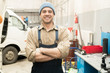 Portrait of young Caucasian male auto mechanic standing in repair shop with crossed hands and smiling at camera cheerfully