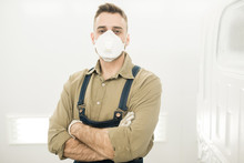 Portrait Of Young Male Auto Technician In Protective Mask Standing In Repair Shop With Crossed Hands And Looking At Camera