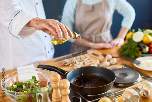 Foto op Plexiglas Koken Close-up of male chef pouring oil into the pan