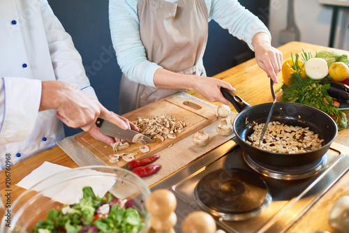 Photo sur Aluminium Cuisine Two cooks cutting and frying mushrooms in the kitchen