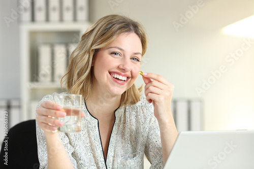 Fotografia  Happy office worker showing a vitamin supplement pill
