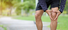 Young Fitness Man Holding His Sports Leg Injury, Muscle Painful During Training. Asian Runner Having Knee Ache And Problem After Running And Exercise Outside In Summer