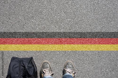 Valokuva  Ein Mann mit einem Koffer steht an der Grenze zu Deutschland