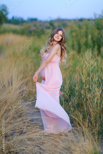 Fotografía  Pregnant young female person wearing pink dress standing in steppe background