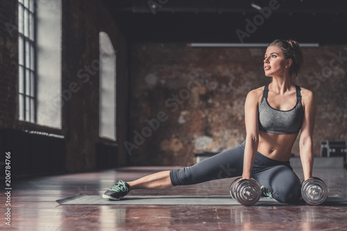 Young sporty girl with dumbbells - 206784766