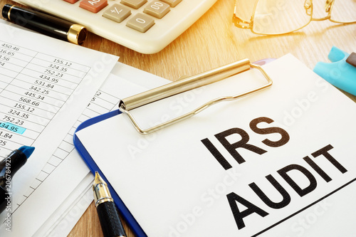 Photo IRS audit documents with clipboard on a desk.