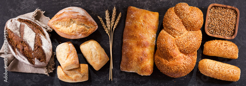 fresh bread with wheat ears on dark table, top view
