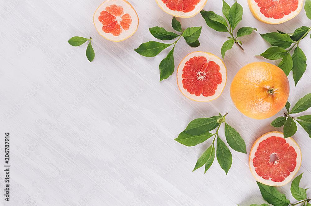 Fotografie, Obraz Summer colorful fresh background - slice grapefruit and green leaves on white wood board