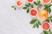 Summer Colorful Fresh Background - Slice Grapefruit And Green Leaves On White Wood Board.