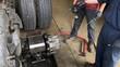 Men working on brakes of transport truck in repair shop