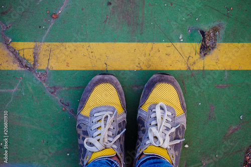 Photo  Legs in yellow sneakers at the yellow line