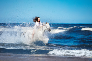 Girl on a white horse storming through the water