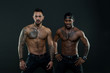Machos with muscular tattooed torsos look attractive, dark background. Athletes on confident faces with nude muscular chests. Guys sportsmen with sexy muscular torsos. Masculinity concept