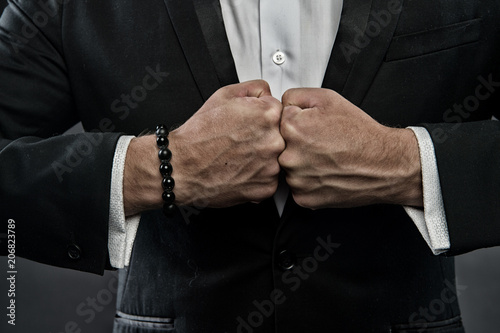Obraz na płótnie Male fists with swollen veins and bracelet on formal suit background