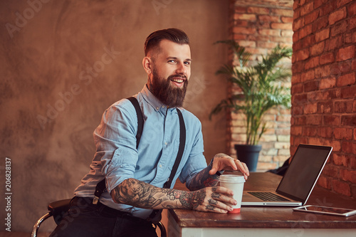Happy handsome tattooed hipster in a shirt and suspenders holds takeaway coffee while sitting at the desk, working on a laptop in an office with a loft interior Canvas Print