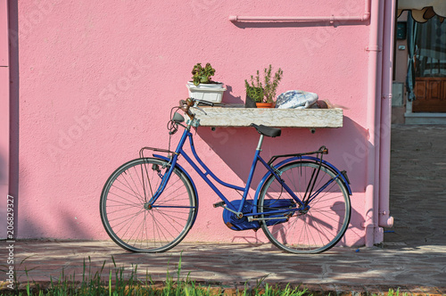 Ingelijste posters Fiets Close-up of bicycle leaning against colorful wall on a sunny day in Burano, a gracious little town full of canals, near Venice. Located in the Veneto region, northern Italy
