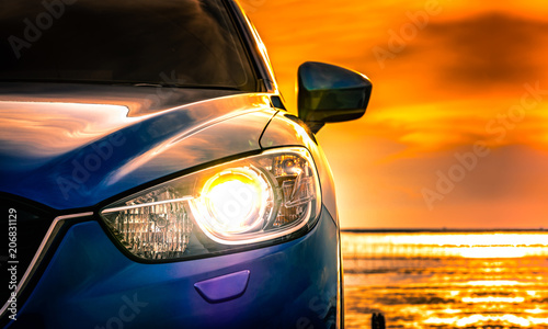 Poster Voitures rapides Blue compact SUV car with sport and modern design parked on concrete road by the sea at sunset. Environmentally friendly technology. Business success concept. Car with open headlamp light.
