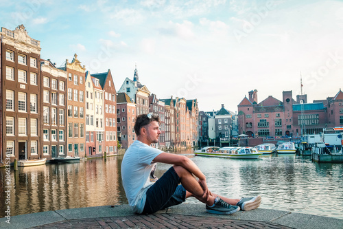 Photo  happy young man at waterfront canal Amsterdam during sunset