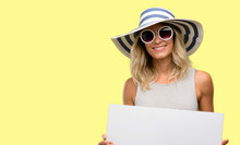 Young Woman Wearing Sunglasses And Summer Hat Holding Blank Advertising Banner, Good Poster For Ad, Offer Or Announcement, Big Paper Billboard