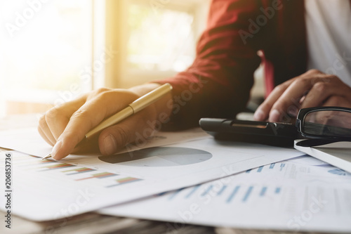 Fototapeta Close up of businessman or accountant hand holding pen working on calculator to calculate financial data report, accountancy document and laptop computer at office, business concept obraz
