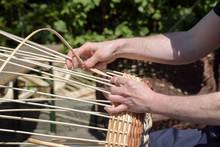 Hands Of A Basket Maker Weave A Wicker Basket