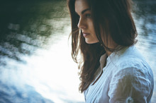 Close Up Portrait Of Beautiful Sensual Young Woman With Brunette Hair Wearing White Dress Sitting Near The Lake In The Forest